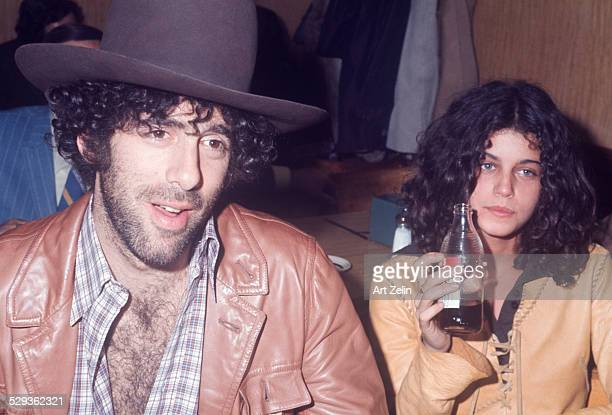 Elliott Gould and Jennifer Bogart sitting at a table in a diner wearing leather jackets circa 1970 New York