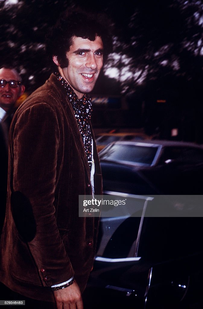 Elliott Gould in a brown velvet jacket getting into a limousine circa 1970 New York