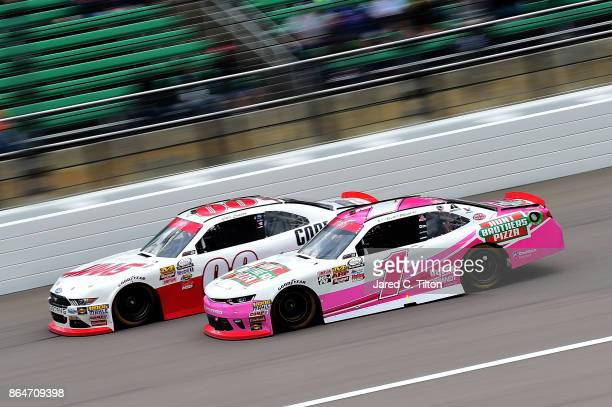 Elliott Sadler driver of the Hunt Brothers Pizza Chevrolet races Cole Custer driver of the Haas/Code 3 Associates Ford during the NASCAR XFINITY...
