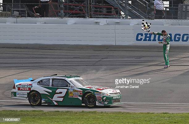 Elliott Sadler driver of the Hunt Brothers Pizza Chevrolet waves the checkered flag after winning the NASCAR Nationwide Series STP 300 at Chicagoland...
