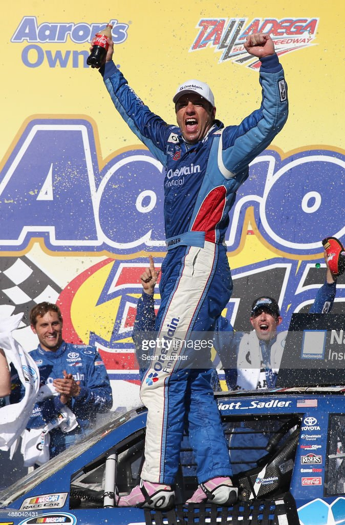 Elliott Sadler driver of the OneMain Financial Toyota celebrates in Victory Lane after winning the NASCAR Nationwide Series Aaron's 312 at Talladega...