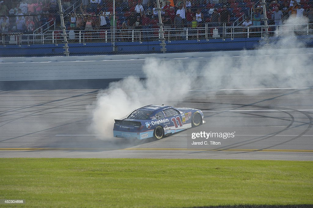 Elliott Sadler driver of the OneMain Financial Toyota celebrates with a burnout after winning during the NASCAR Nationwide Series Aaron's 312 at...