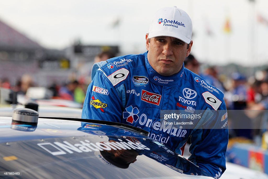 Elliott Sadler driver of the OneMain Financial Toyota gets in his car during qualifying for the NASCAR Nationwide Series Aaron's 312 at Talladega...