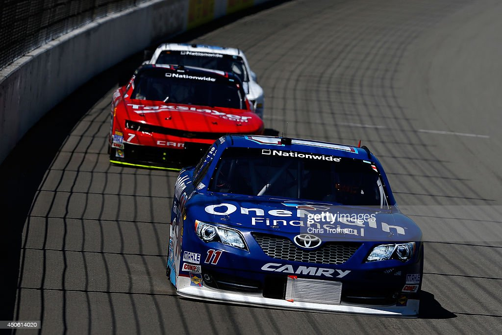 Elliott Sadler, driver of the #11 OneMain Financial Toyota, leads Regan Smith, driver of the #7 TaxSlayer.com Chevrolet, into turn one during the NASCAR Nationwide Series Ollie's Bargain Outlet 250 at Michigan International Speedway on June 14, 2014 in Brooklyn, Michigan.