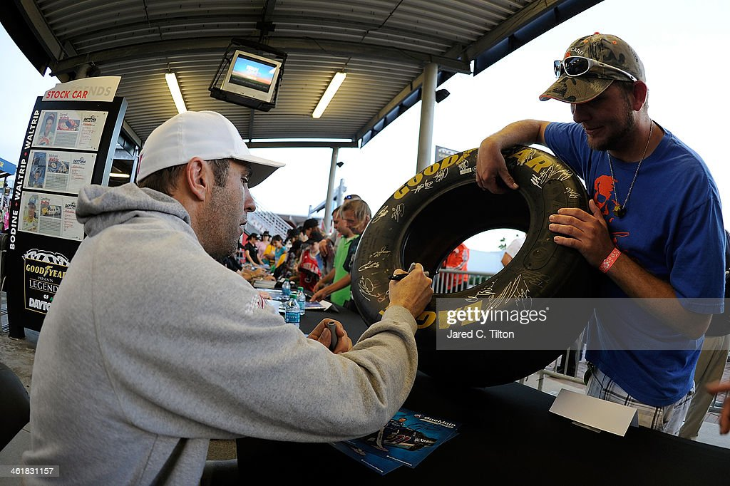 Elliott Sadler, driver of the #11 OneMain Financial Toyota, signs autographs along with other Nationwide Series drivers during NASCAR Preseason Thunder at Daytona International Speedway on January 11, 2014 in Daytona Beach, Florida.