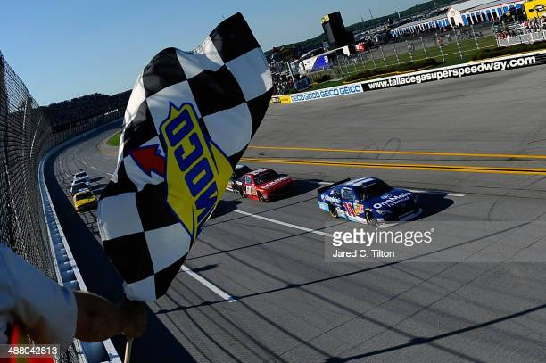 Elliott Sadler driver of the OneMain Financial Toyota takes the checkered flag to win the NASCAR Nationwide Series Aaron's 312 at Talladega...