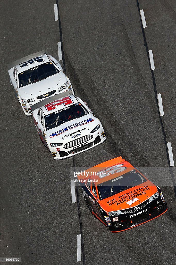Elliott Sadler, driver of the #55 RK Motors Collector Car Auctions Toyota, leads Ken Schrader, driver of the #32 U.S. Chrome Ford, and JJ Yeley, driver of the #36 Tommy Baldwin Racing Chevrolet, during the NASCAR Sprint Cup Goody's Headache Relief Shot 500 Powered By Kroger at Martinsville Speedway on October 27, 2013 in Martinsville, Virginia.