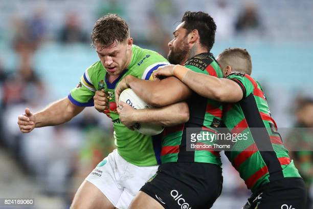 Elliott Whitehead of the Raiders is tackled by John Sutton of the Rabbitohs during the round 21 NRL match between the South Sydney Rabbitohs and the...
