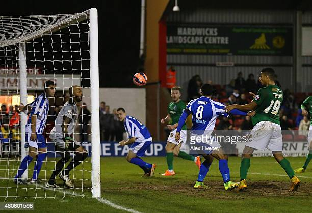 Ellis Deeney and Nathan Vaughan of Worcester City fail to keep the ball out of the net as Paddy Madden of Scunthorpe United scores the opening goal...