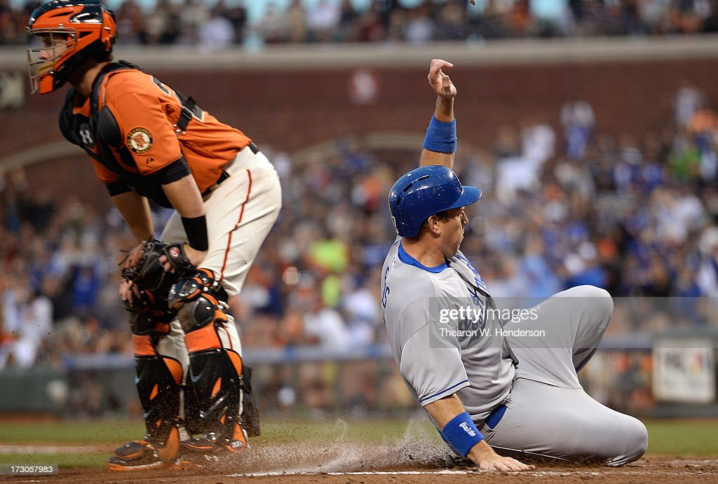 A.J. Ellis #17 of the Los Angeles Dodgers scores all the way from first base on a bases loaded triple from Juan Uribe #5 as catcher Buster Posey #28 of the San Francisco Giants looks on in the third inning at AT&T Park on July 5, 2013 in San Francisco, California.