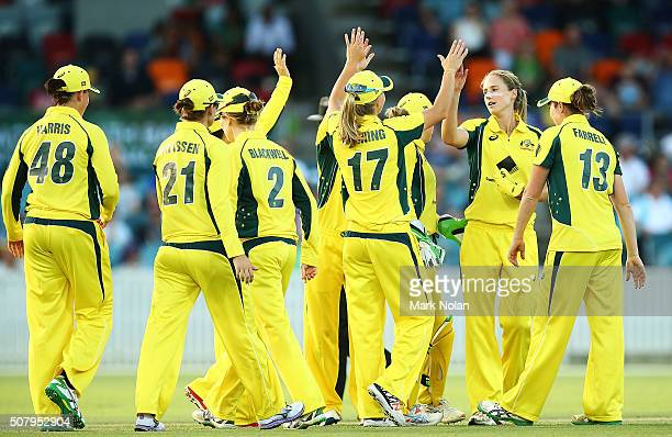 Ellyse Perry of Australia celebrates a wicket with tem mates during game one of the Women's ODI series between Australia and India at Manuka Oval on...