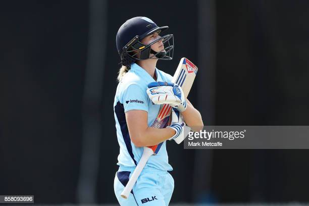 Ellyse Perry of NSW walks from the field after caught by Beth Mooney of Queensland off the bowling of Delissa Kimmince of Queensland during the WNCL...