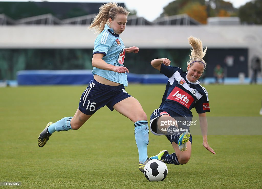 Ellyse Perry of Sydney FC kicks the ball away from Katie Hoyle of the Victory during the round one W-League match between the Melbourne Victory and Sydney FC at Lakeside Stadium on November 10, 2013 in Melbourne, Australia.