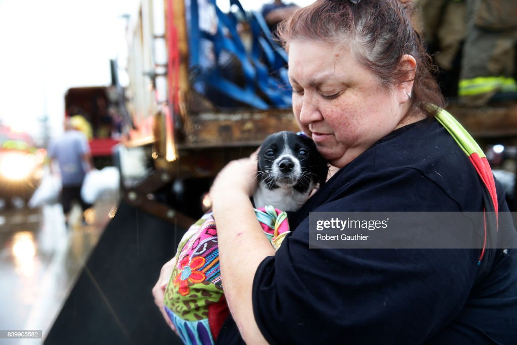 Elma Moreno comforts her dog, Simon as they are loaded on to a trucks after being evacuated from their flooded apartment. Tropical Storm Harvey is causing major flooding throughout Houston and Southeast Texas.