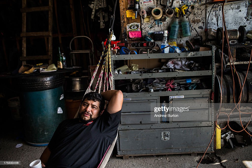 Elmer Bautista relaxes in a hammock due to a lack of work on August 2, 2013 in the Willet's Point neighborhood of the Queens borough of New York City. The neighborhood has been in a battle with the city of New York for years, which plans to demolish the neighborhood and invest $3 billion for a mall, apartments and more parking for nearby Citi Field. Members of the neighborhood argue that over two hundred small businesses are established in the neighborhood and should not be evicted.
