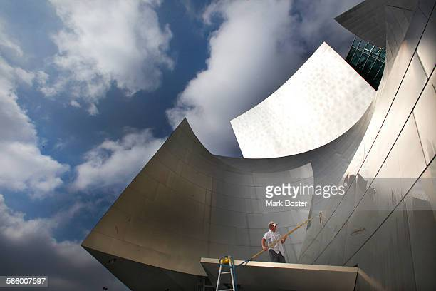 Elmer Paiz washes the shiney exterior metal surfaces of the Walt Disney Concert Hall on a cloudy day in Los Angeles May 4 2012