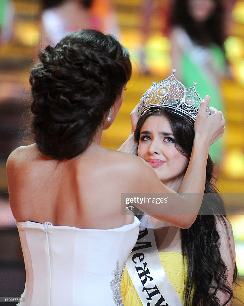 Elmira Abdrazakova (R) is crowned as Miss Russia 2013 by Miss Russia 2012 Elizaveta Golovanova (L) during the competion in Moscow late on March 2, 2013. The 18-year-old Abdrazakova from Mezhdurechensk was crowned the 2013 winner in the 21st edition of Miss Russia.