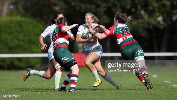 Eloise Bloomfield of Saracens Women is tackled by Lauren Delaney and Michelle Davis of Firwood Waterloo Ladies during the Tyrrells Premier 15 at The...