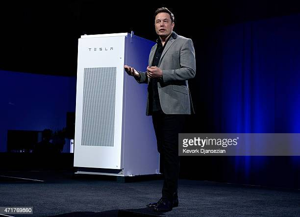 Elon Musk CEO of Tesla with a Powerpack unit the background unveils suit of batteries for homes businesses and utilities at Tesla Design Studio April...