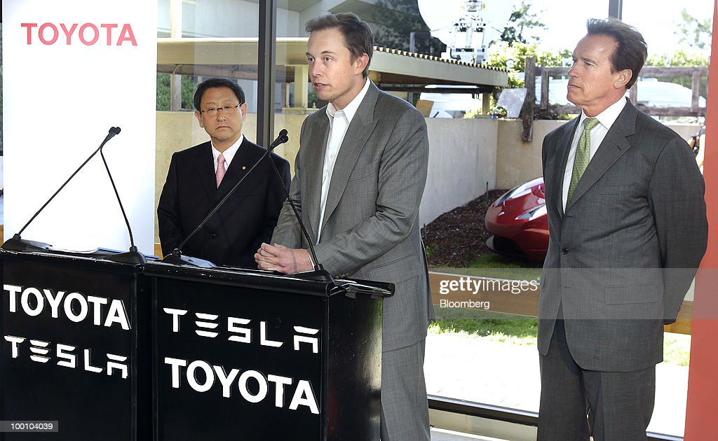 Elon Musk, chairman and chief executive officer of Tesla Motors Inc., center, speaks as Akio Toyoda, president of Toyota Motor Corp., left, and Arnold Schwarzenegger, governor of California, listen during a news conference at the Tesla Motors Inc. headquarters in Palo Alto, California, U.S., on Thursday, May 20, 2010. Toyota Motor Corp. will acquire a $50 million stake in California electric-car maker Tesla Motors Inc. as automakers compete to introduce less-polluting vehicles in the U.S. Photographer: Tony Avelar/Bloomberg via Getty Images