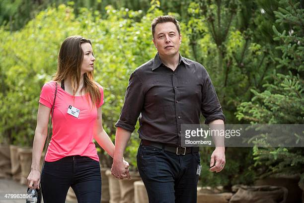 Elon Musk chairman and chief executive officer of Tesla Motors Inc and his wife Talulah Riley walk the grounds after a morning session during the...