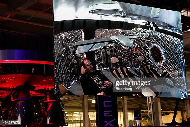 Elon Musk chief executive officer of Space Exploration Technologies Corp is seen inside the capsule on a screen during the unveiling of the Manned...