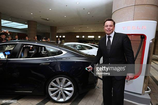 Elon Musk cofounder and chief executive officer of Tesla Motors Inc holds the charging nozzle as he demonstrates the company's Model S electric sedan...