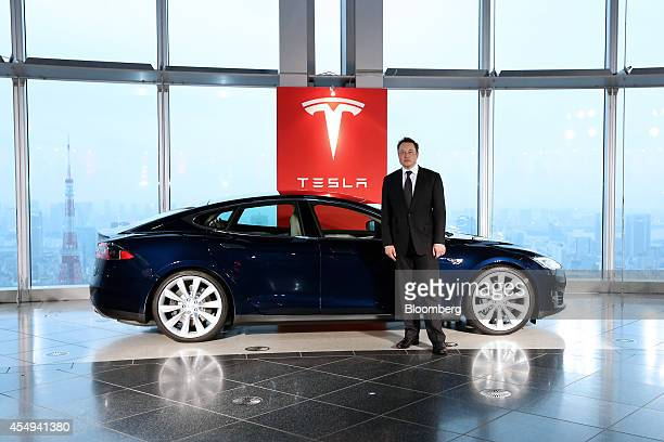 Elon Musk cofounder and chief executive officer of Tesla Motors Inc stands in front of the company's Model S electric sedan following a key delivery...
