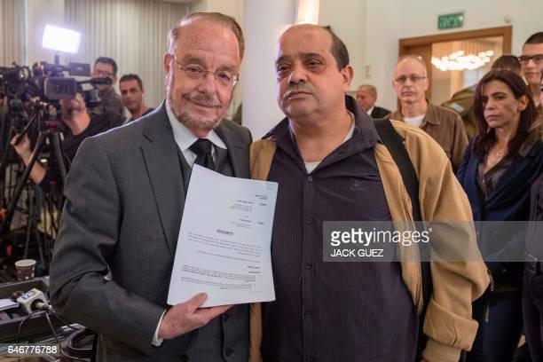 Elor Azaria's father Charlie and defence attorney Yoram Sheftel show a notice of appeal before holding a press conference on March 1 in the Israeli...