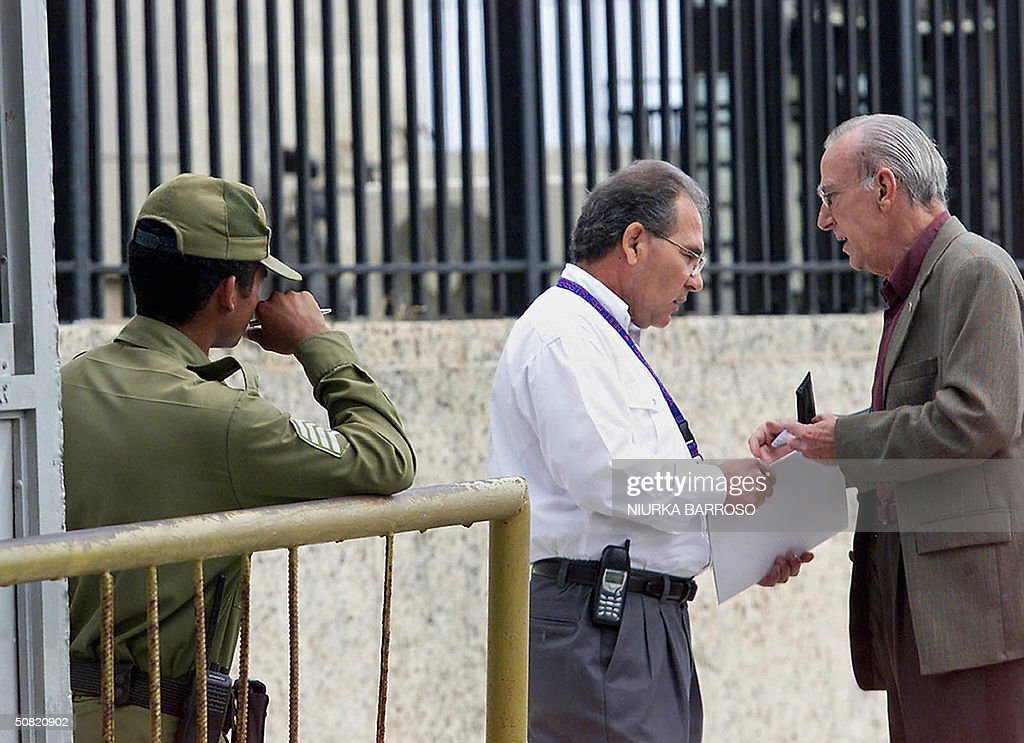 Eloy Gutierrez Menoyo (R) Former Commander of the Revolution and President of the Organisation 'Cambio Cubano', speaks with an employee while delivering a document at the entrance of the United States Interest Office in Havana, 10 May 2004. The document addressed Secretary of State Colin Powell rejecting either economic and political measures on Cuba. Gutierrez Menoyo spent 22 years in prision and emigrated to the US returning in 2003 to Cuba to fight against government from inside. AFP PHOTO/Niurka BARROSO