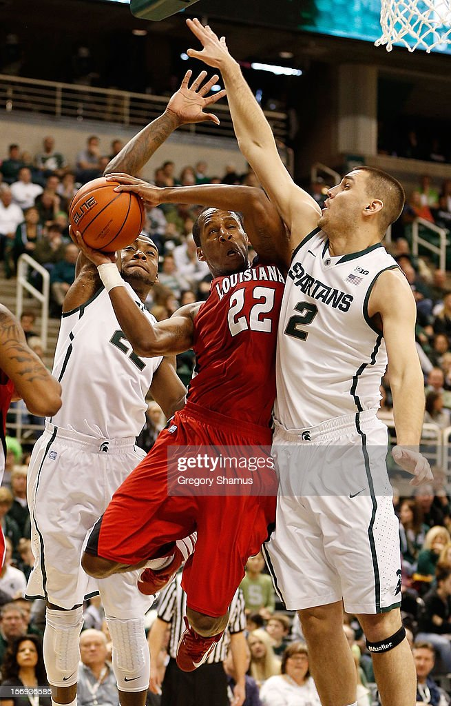 Elridge Moore #22 of the Louisiana-Lafayette Ragin' Cajuns tries to get a second half shot off between Alex Gauna #2 and Branden Dawson #22 of the Michigan State Spartans at the Jack T. Breslin Student Events Center on November 25, 2012 in East Lansing, Michigan.