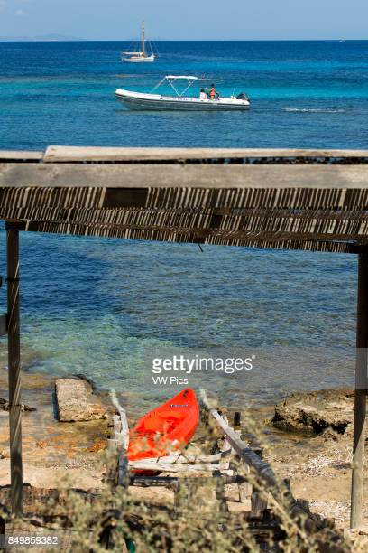 Els Pujols beach in Formentera with traditional fishing boat and kayaks in summer day LlaÙt boats