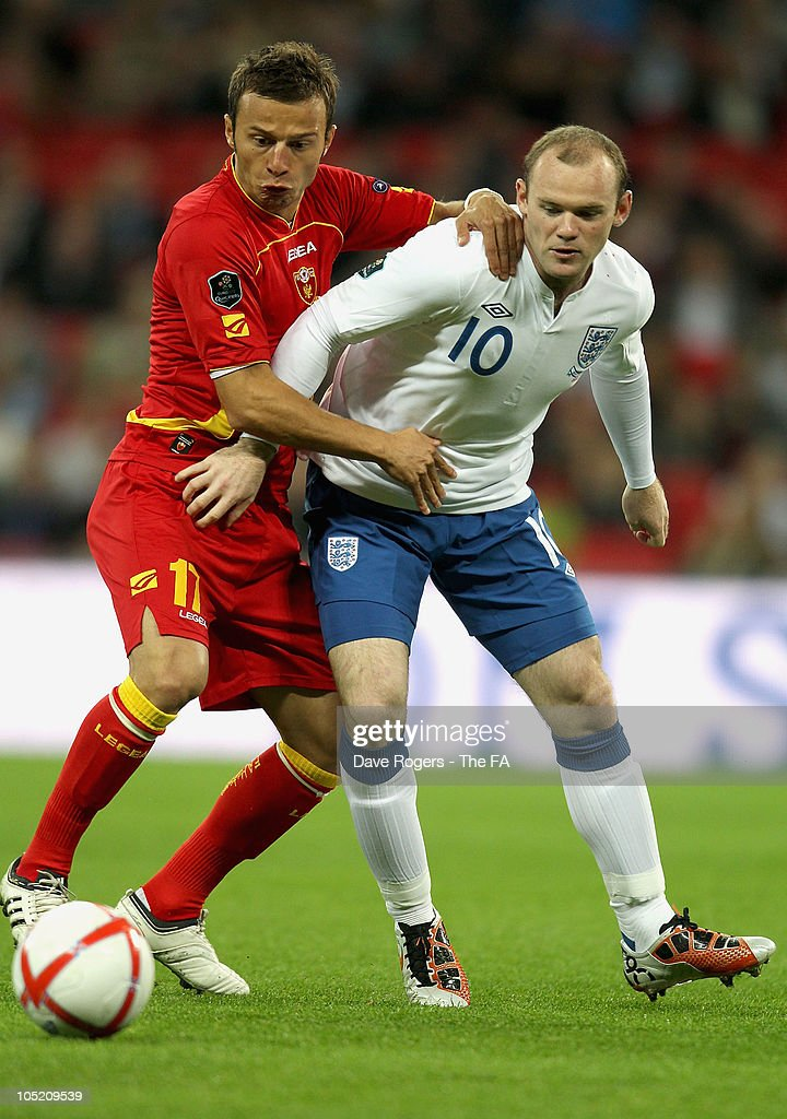 Elsad Zverotic of Montenegro and <a gi-track='captionPersonalityLinkClicked' href=/galleries/search?phrase=Wayne+Rooney&family=editorial&specificpeople=157598 ng-click='$event.stopPropagation()'>Wayne Rooney</a> of England in action during the UEFA EURO 2012 Group G Qualifying match between England and Montenegro at Wembley Stadium on October 12, 2010 in London, England.