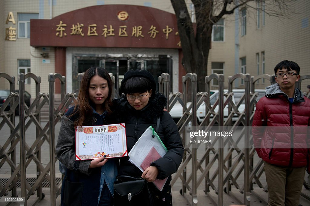 Elsie Liao (L) and Mayu Yu (R) hold a mock marriage certificate outside the registry office where they asked to be married, before being turned away, in Beijing on February 25, 2013. Although not in a relationship together, the pair sought to draw attention to China's stance on same-sex marriage which is not recognised by law, the lack of access to social benefits available to couples, and to promote public awareness of discrimination against the LGBT community. China's government has an un-verified but widely reported 'three no's' policy towards homosexuality; no approval, no disapproval, no promotion. Same-sex acts were decriminalised in China in 1997, and homosexuality was removed from the country's mental illness list in 2001. As of June 2012 a 14-year-old ban was lifted allowing lesbians, although not gay men, to give blood. AFP PHOTO / Ed Jones