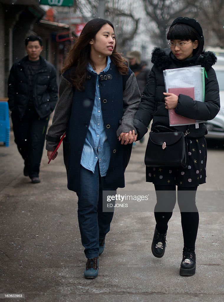Elsie Liao (C) and Mayu Yu (R) leave the registry office where they asked to be married, before being turned away, in Beijing on February 25, 2013. Although not in a relationship together, the pair sought to draw attention to China's stance on same-sex marriage which is not recognised by law, the lack of access to social benefits available to couples, and to promote public awareness of discrimination against the LGBT community. China's government has an un-verified but widely reported 'three no's' policy towards homosexuality; no approval, no disapproval, no promotion. Same-sex acts were decriminalised in China in 1997, and homosexuality was removed from the country's mental illness list in 2001. As of June 2012 a 14-year-old ban was lifted allowing lesbians, although not gay men, to give blood. AFP PHOTO / Ed Jones