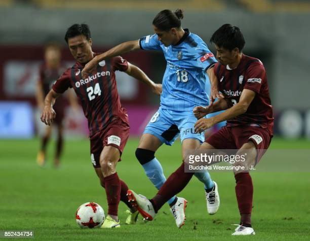 Elsinho of Kawasaki Frontale competes for the ball against Masatoshi Mihara and Hirofumi Watanabe of Vissel Kobe during the JLeague J1 match between...
