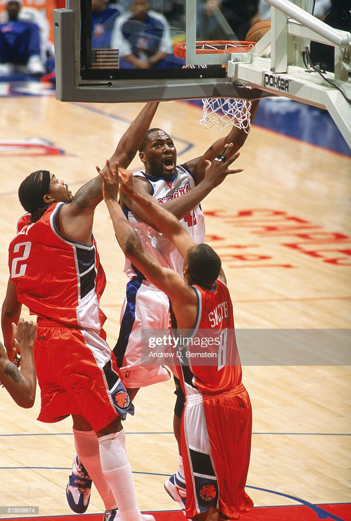 Elton Brand of the Los Angeles Clippers takes the ball the basket between Melvin Ely and Steve Smith of the Charlotte Bobcats during a game at...
