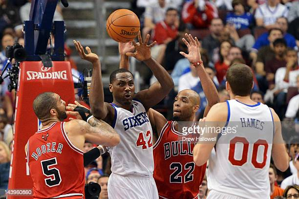 Elton Brand of the Philadelphia 76ers dishes off a pass to teammate Spencer Hawes while being pressure by Carlos Boozer and Taj Gibson of the Chicago...