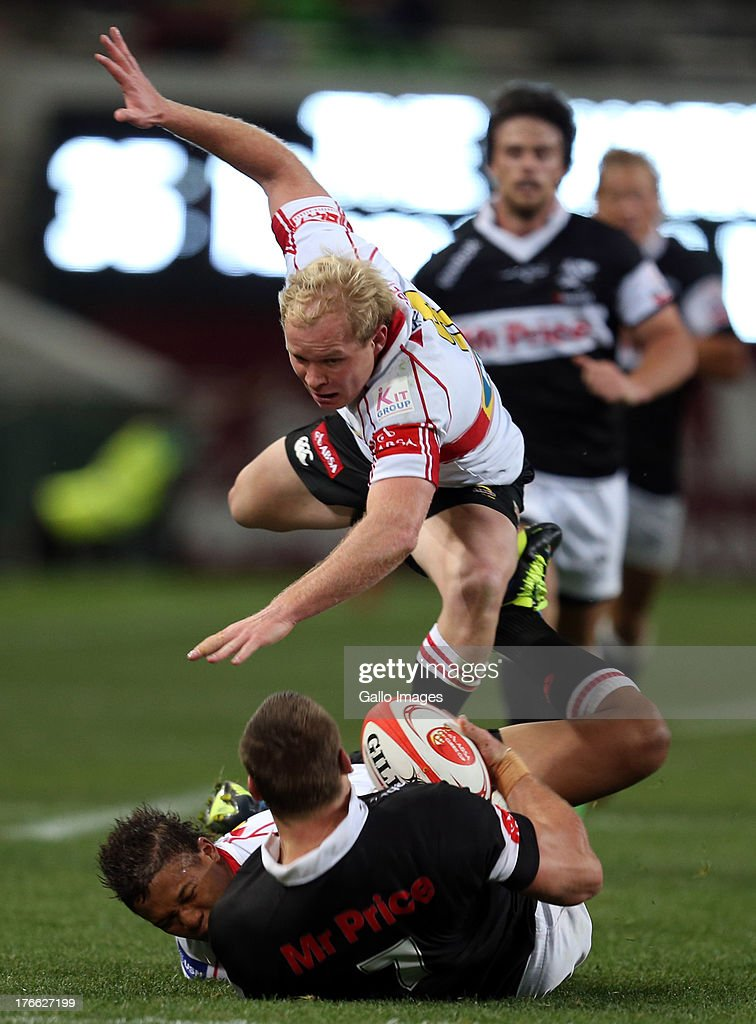 Elton Jantjies of the Lions tackling Jean Deysel of the Sharks and Guy Cronje of the Lions over the top during the Absa Currie Cup match between The Sharks and MTN Golden Lions at Growthpoint Kings Park on August 16, 2013 in Durban, South Africa.