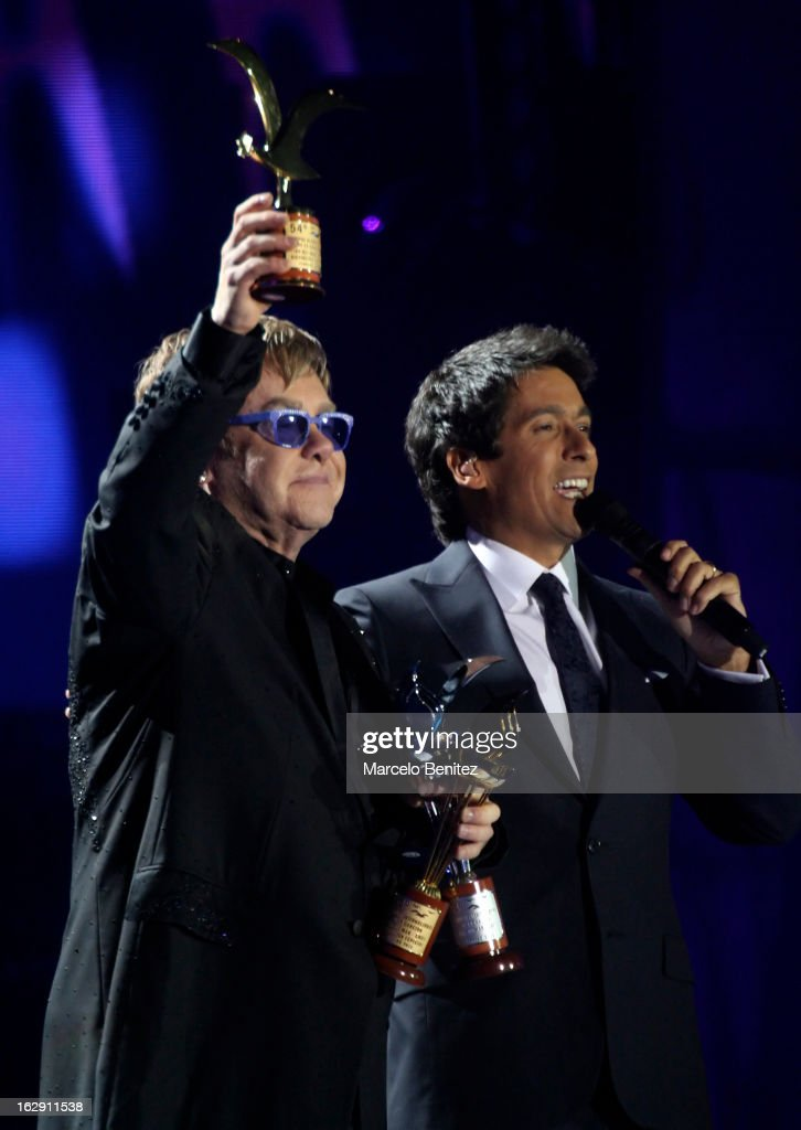 Elton Jhon holds his award next to Rafael Araneda during his presentation on stage at the 53rd Vina del Mar International Music Festival 2013 on February 28, 2013 in Viña del Mar, Chile.