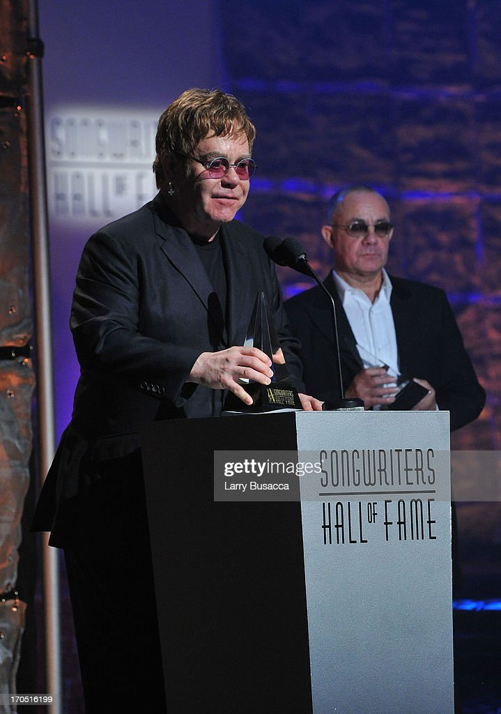 <a gi-track='captionPersonalityLinkClicked' href=/galleries/search?phrase=Elton+John&family=editorial&specificpeople=171369 ng-click='$event.stopPropagation()'>Elton John</a> and <a gi-track='captionPersonalityLinkClicked' href=/galleries/search?phrase=Bernie+Taupin&family=editorial&specificpeople=669725 ng-click='$event.stopPropagation()'>Bernie Taupin</a> speak at the Songwriters Hall of Fame 44th Annual Induction and Awards Dinner at the New York Marriott Marquis on June 13, 2013 in New York City.