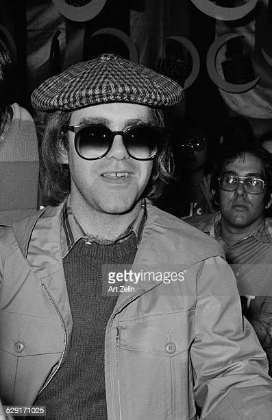 Elton John in cap and sunglasses signing autographs circa 1970 New York