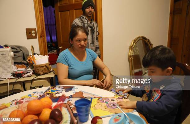 Elvira Arellano helps her youngest son Emiliano Mejia with a puzzle while his father Ismael Armando Mejia looks on in their apartment Tuesday March...