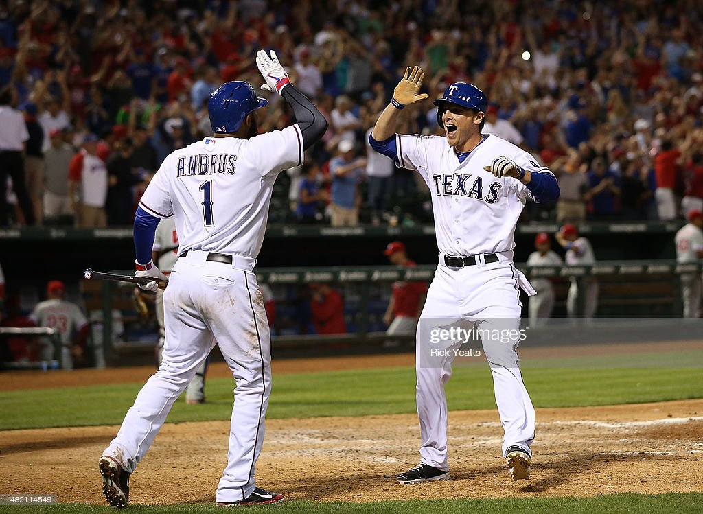 Elvis Andrus celebrates with Jim Adduci of the Texas Rangers as he scores the winning run on a walk on ShinSoo Choo in the ninth inning against the...