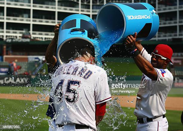 Elvis Andrus of the Texas Rangers and Martin Perez of the Texas Rangers soak Derek Holland of the Texas Rangers with Powerade after Holland threw a...