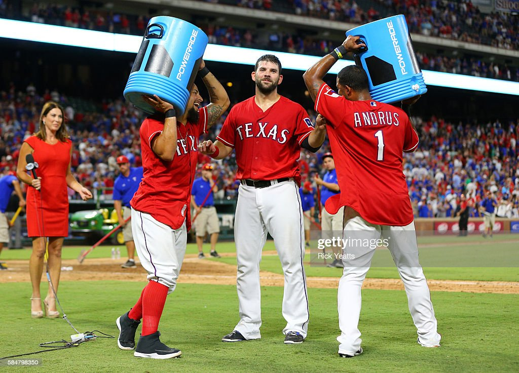 Elvis Andrus #1 of the Texas Rangers and Rougned Odor #12 circle Mitch Moreland #18 with the coolers after Moreland walk off home run against the Kansas City Royals at Globe Life Park in Arlington on July 30, 2016 in Arlington, Texas.