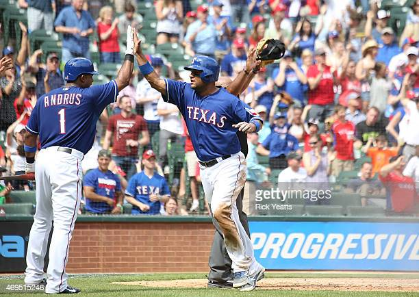 Elvis Andrus of the Texas Rangers celebrates with Carlos Corporan for scoring in the seventh inning against the Houston Astros at Globe Life Park in...