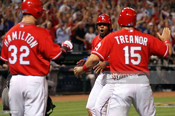 Elvis Andrus of the Texas Rangers celebrates with Matt Treanor and Josh Hamilton after scoring in the fourth inning against the New York Yankees in...