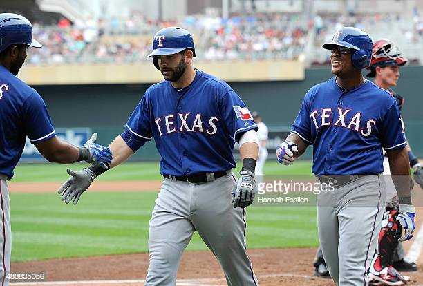 Elvis Andrus of the Texas Rangers congratulates teammates Mitch Moreland and Adrian Beltre on scoring against the Minnesota Twins on a tworun home...