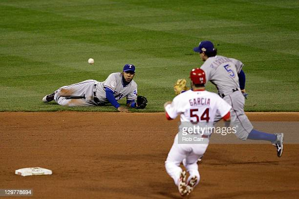 Elvis Andrus of the Texas Rangers flips the ball to Ian Kinsler for a fielders choice out to get Jaime Garcia of the St Louis Cardinals at second...